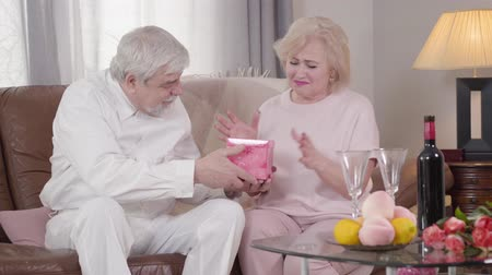 pocałunek : Mature Caucasian man giving gift box to his lovely beautiful wife in Saint Valentines Day. Grateful woman smiling and kissing husband on cheek. Happy spouses spending Saint Valentines Day at home