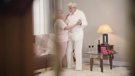 dankbaar : Long shot of mature Caucasian married couple talking and dancing at home. Happy senior retirees celebrating Saint Valentines Day indoors. Eternal love of elegant spouses. Unity, bonding, lifestyle