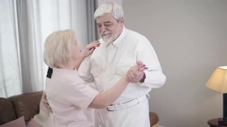 agradecido : Middle shot of smiling mature Caucasian husband and wife dancing at home. Happy senior couple in love spending Saint Valentines Day indoors. Joy, happiness, romance, eternal love