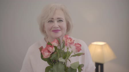 egyetlen virág : Close-up portrait of beautiful Caucasian mature woman smelling bouquet of roses, looking at camera and smiling. Happy senior female retiree posing with Saint Valentines Day gift indoors