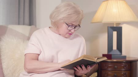 čtenář : Portrait of senior Caucasian blond woman in eyeglasses reading book at home. Mature smart woman resting indoors in the evening. Hobby, lifestyle, literature