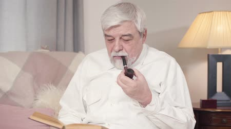 literatuur : Portrait of grey-haired Caucasian man smoking pipe and reading book at home. Mature serious man spending quiet evening indoors. Leisure, hobby, lifestyle Stockvideo