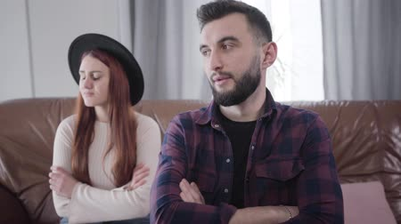annoyance : Portrait of young handsome Caucasian man with brown eyes and brunette hair sitting with crossed hands as his sad wife or girlfriend crying at the background. Concept of relationship problems, breakup, divorce