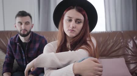 culpado : Portrait of young nervous Caucasian woman pulling back hand of husband or boyfriend calming her down. Beautiful elegant girl angry at spouse, guilty man apologizing. Lifestyle, marriage, problems Stock Footage