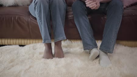 divadelní : Close-up of unrecognizable man and woman without boots sitting on couch and moving feet. Young anxious couple waiting for psychological consultation. Worry, problems solution, counselling