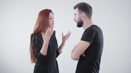 unalom : Young irritated Caucasian couple in black clothes arguing at white background. Handsome bearded man and beautiful redhead woman quarreling. Marriage difficulties, relationship problems, conflict