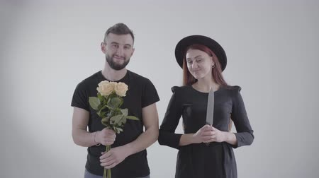 színpadi : Young beautiful Caucasian couple looking at each other and smiling as holding big knife and bouquet of yellow roses in hands. People turning heads and stretching flowers and chopper at camera