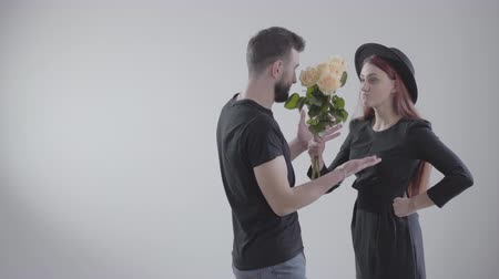 irritação : Elegant offended Caucasian girl in black dress and hat beating her boyfriend or husband with flowers. Young handsome man leaving the shot with bouquet. Conflict of young couple at white background