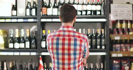 kırmızı şarap : Back view of young bearded Caucasian man examining shelves with wine bottles. Sommelier selecting best drink for evening in wine shop. Lifestyle, consumerism, profession