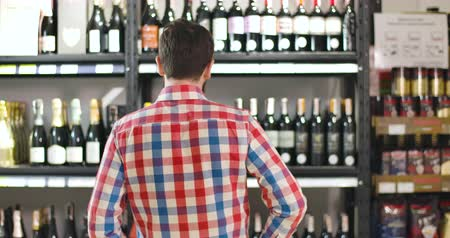 kırmızı şarap : Back view of man scratching head as looking at shelves with bottles of wine. Confused Caucasian customer selecting drink in luxurious wine shop. Alcohol, beverage, consumerism, lifestyle