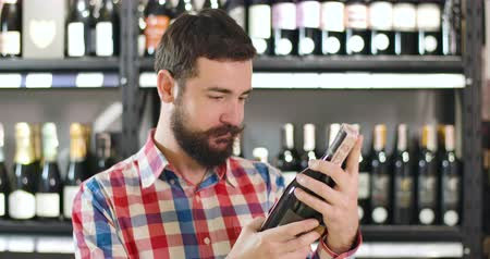 kırmızı şarap : Close-up of young confident Caucasian man reading label on wine bottle and looking back at shelves. Professional sommelier selecting luxurious drink in store. Confidence, lifestyle, alcohol industry