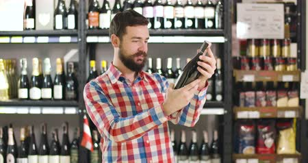 kırmızı şarap : Young cheerful Caucasian man looking at label on wine bottle, hugging drink, looking at camera and smiling. Satisfied customer buying alcohol in luxurious store. Lifestyle, happiness, beverage