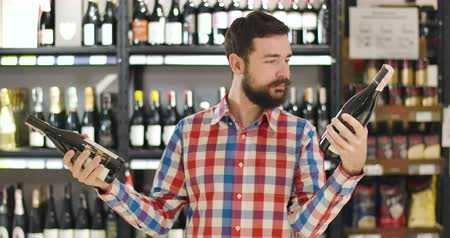 alışveriş : Confused young Caucasian man holding two bottles of wine in both hands and reading labels. Positive bearded guy showing I dont know gesture and smiling at camera, Choice, luxurious alcohol, lifestyle