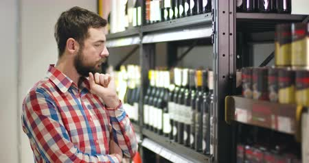 kırmızı şarap : Side view of thoughtful bearded Caucasian man looking at shelves with wine bottles and scratching head. Concentrated young guy choosing alcohol in luxurious store. Alcohol industry, lifestyle, wealth Stok Video