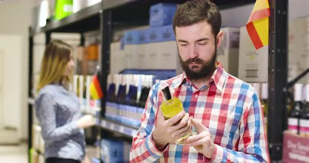 supermarket shelf : Portrait of young handsome Caucasian man examining label on bottle of expensive white wine in shop as blurred slim woman choosing drink on shelves at the background. People buying beverage in store