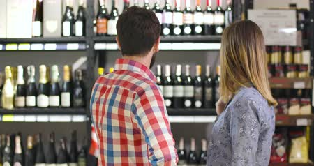 kırmızı şarap : Back view of young Caucasian couple in love choosing luxurious wine in store. Man and woman standing in front of shelves with alcohol, looking at each other, smiling, and gesturing yes by shaking head