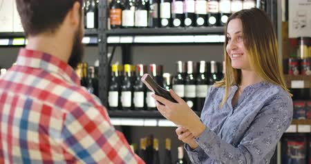 kırmızı şarap : Portrait of young smiling Caucasian woman talking with unrecognizable salesman or sommelier in luxurious wine market. Rich beautiful girl selecting alcohol drink in store. Lifestyle, wealth, happiness