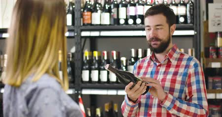 kırmızı şarap : Portrait of brunette bearded Caucasian man with grey eyes presenting new wine to unrecognizable female customer in luxurious store. Young salesman or sommelier working in alcohol market Stok Video