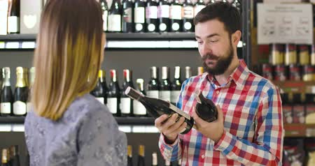 kırmızı şarap : Portrait of excited young Caucasian man holding two bottles of red wine and talking with unrecognizable woman. Confident bearded salesman or sommelier helping client to choose drink in alcohol shop