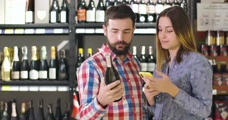 authenticity : Serious adult Caucasian man and woman comparing label on wine bottle with information in phone. Modern couple verifying authenticity of drink using modern technologies. Consumerism, alcohol industry Stock Footage