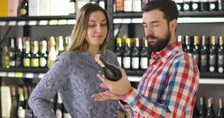 kırmızı şarap : Caucasian man and woman discussing red wine as standing at the background of shelves with bottles in luxurious alcohol shop. Young family choosing beverage in store. Joy, lifestyle, industry