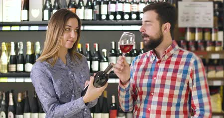 lussuoso : Portrait of confident young Caucasian man tasting red wine from glass as smiling brunette woman standing next to him with bottle in front of shelves with alcohol. Sommelier degustating drink in shop