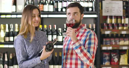 kırmızı şarap : Young male Caucasian sommelier smelling red wine in glass and looking at drink on light. Professional degustating beverage in luxurious wine market. Lifestyle, occupation, profession Stok Video