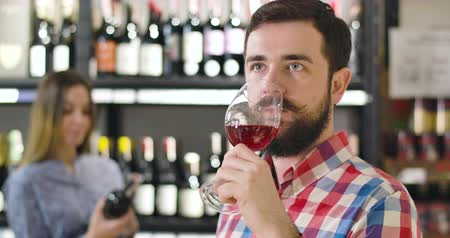 kırmızı şarap : Close-up of handsome confident Caucasian man with beard tasting red wine from glass. Professional sommelier degustating alcohol drink in store, Profession, occupation, lifestyle
