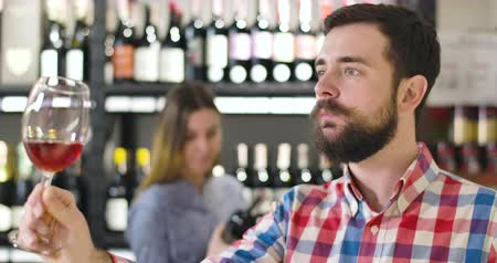 kırmızı şarap : Side view of professional concentrated sommelier shaking glass with red wine. Young confident Caucasian man degustating expensive drink in luxurious alcohol shop. Degustation, occupation, lifestyle