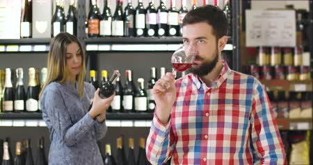 kırmızı şarap : Portrait of young professional sommelier smelling expensive red wine in glass and showing thumb up. Confident bearded Caucasian man certificating luxurious drinks in alcohol shop