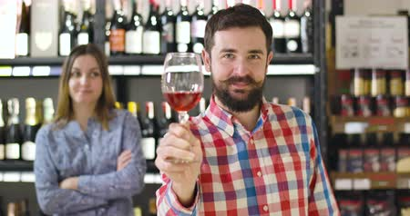 kırmızı şarap : Happy smiling Caucasian man smelling red wine, stretching glass to camera, and drinking alcohol. Joyful professional sommelier degustating beverage in expensive shop. Joy, occupation, lifestyle