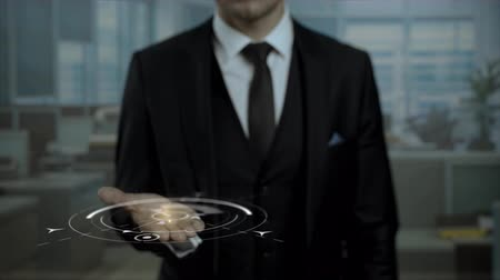 targeting : Corporate marketing expert presenting strategy Brand Development using hologram. Entrepreneur in black suit holding cyber Earth with words on his hand. Stock Footage