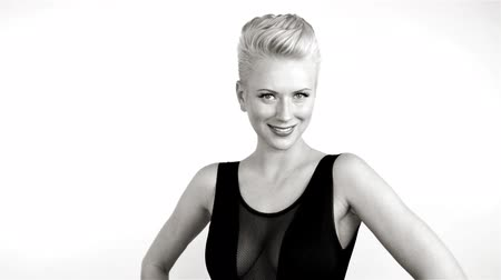 Beautiful young blonde girl with short hair wearing a black dress with bare shoulders smiling expresses emotions joy sexy tenderness Stock mozgókép