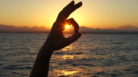 taça : hand showing Ok sign in silhouette against sun