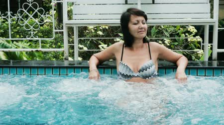 джакузи : slow motion video of a attractive woman relaxing in the jacuzzi