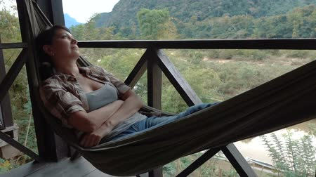 гамак : Woman relax in a hammock overlooking the mountains and the river. Full HD slow motion stock footage. Стоковые видеозаписи