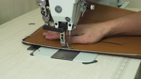 industry : Closeup view of mans hand stitching leather product with modern sewing machine. Making a leather handbag. Stock Footage