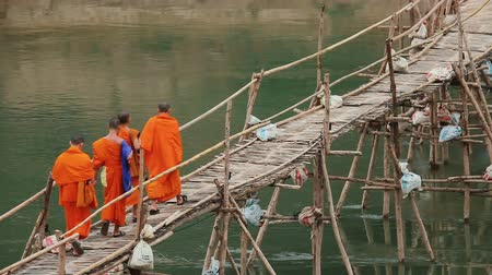prabang : LUANG PRABANG - DECEMBER 19, 2016: Monks walking bamboo bridge over Nam Khan River on december 19, 2016 in Luang Prabang, Laos.