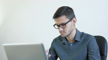 értékesítés : Close-up portrait of a young man wearing glasses sitting in his office in front of a monitor - working on a computer and talking on the phone. People stock footage shot.