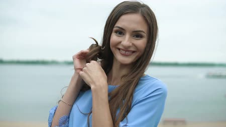 bétula : Young beautiful woman in a blue dress playing with her hair and making a mustache out of it. She poses for the camera, looking very happy. Stock Footage