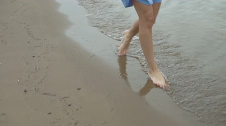 nogi : Young beautiful woman in blue dress walking on the water along the beach. Wideo