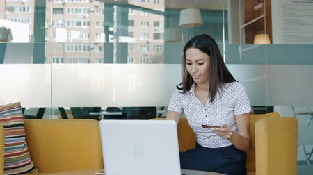 fizet : Portrait of a smiling young woman sitting in front of a monitor. People stock footage shot.