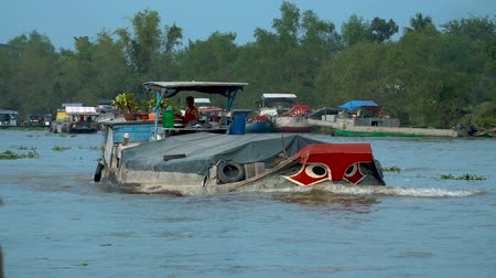 cai : CAI BE - DECEMBER 16, 2017: Heavy loaded boats at the traditional floating market on Mekong delta on December 16, 2017 in Cai Be, Vietnam.