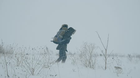 vadon terület : A portrait of a young man with a backpack during a snowstorm in the snowy wilderness, struggling wind and extreme cold. Stock mozgókép