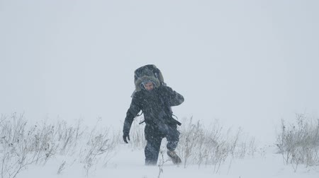 caminhada : Young man with backpack walking through a snowstorm in the snowy wilderness, struggling wind and extreme cold.