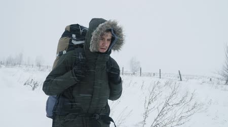 альпинист : Young man with backpack walking through a snowstorm in the snowy wilderness, struggling wind and extreme cold.