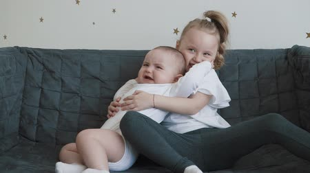 сестры : Portraits of a cute little girl and baby boy hugging on the sofa. Slow motion family concept video. Стоковые видеозаписи