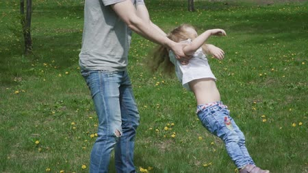 rotates : Circling the child. Father turns his daughter. Family in the park. Slow motion family concept video.