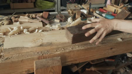 aparas de madeira : Skilled craftsman carpenter whittles workpiece of a wooden board with a jack-plane in a workshop. Making handmade furniture. Vídeos