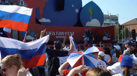 fan zone : SAMARA - JUNE 25, 2018: Slow motion - football fans waving hands and flags, before the game FIFA FAN FEST zone. World Cup 2018 on June 25, 2018 in Samara, Russia. Stock Footage